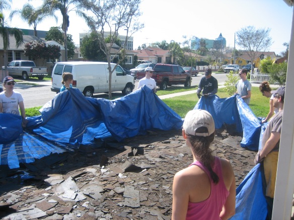 Penn Serves LA volunteers moving a tarp from the lawn Habitat for Humanity Los Angeles