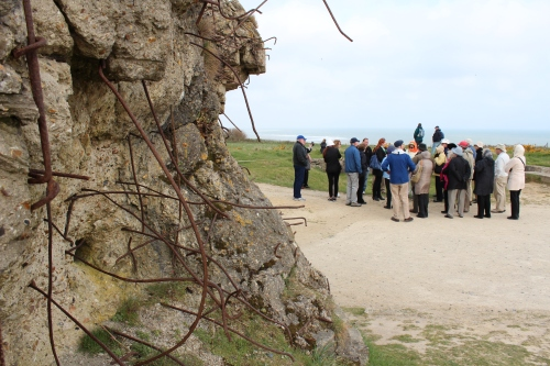 Our tour group listens to our local guide recount the military operation at the Pointe du Hoc.