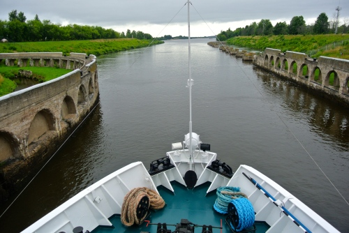 On the ship's prow, traveling along the Russian waterways.