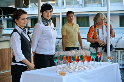The crew offers passengers colored champagne as they depart Kizhi.