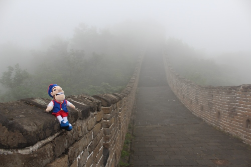 The Quaker sits atop the Great Wall of China during one of his adventures on a Penn Alumni Travel trip.