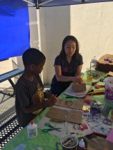 A Penn Serves LA volunteer works on crafts outside with an ICEF student